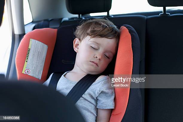 A young boy sleeping in a car seat in the back seat of a car