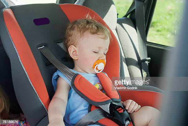 A young boy sleeping in the back seat of a car