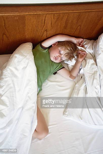 Young boy sleeping on bed