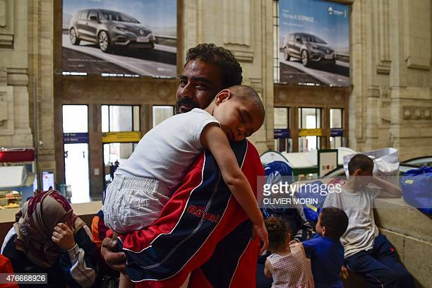 A young boy sleeps in his father's arms at the Milan train station on June 11 as about 300 migrants mainly from Eritrea arrived in Milan late on June...