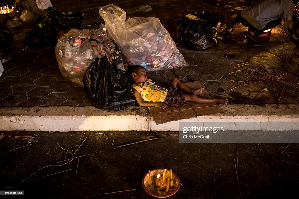 A young boy sleeps on the footpath outside of the Royal Palace after the cremation ceremony for former King Norodom Sihanouk on February 4, 2013 in Phnom Penh, Cambodia. The former King's cremation ceremony comes on the fourth day of a seven day royal funeral ceremony and nearly four months since his death in Beijing last October. Foreign leaders from 16 countries attended the cremation ceremony.