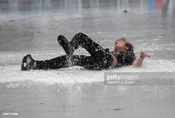 A young boy slips on a huge puddle of water from the melted ice at Bryant Park Ice Skating Rink in New York on November 6 2015 New York City was...