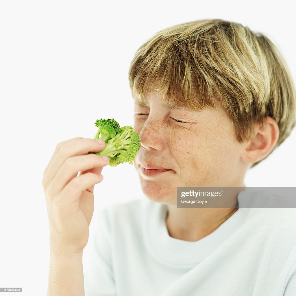 Young boy (12-13) smelling a floret of broccoli : Stock Photo