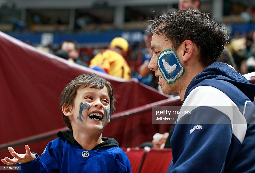 A young boy smiles at his father after a Canucks goal during the NHL game against the Arizona Coyotes at Rogers Arena March 9, 2016 in Vancouver, British Columbia, Canada. Vancouver won 3-2 in overtime.