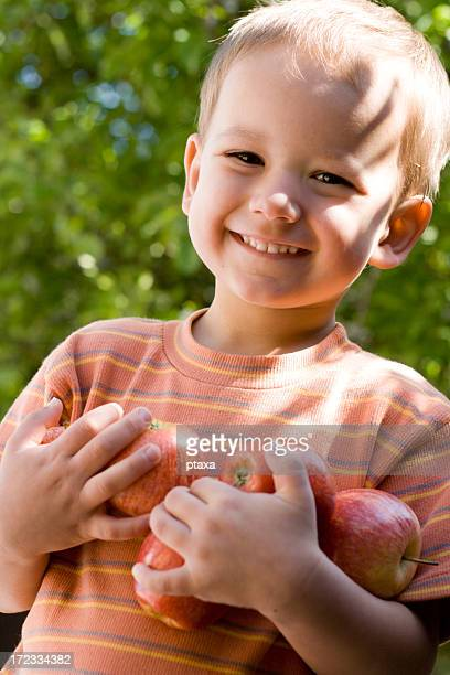 Young boy smiling and holding apples