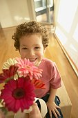 Young boy smiling and offering flowers
