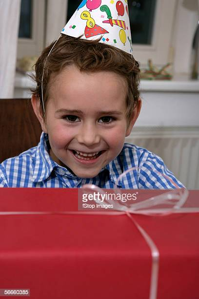 A young boy smiling at a large birthday present