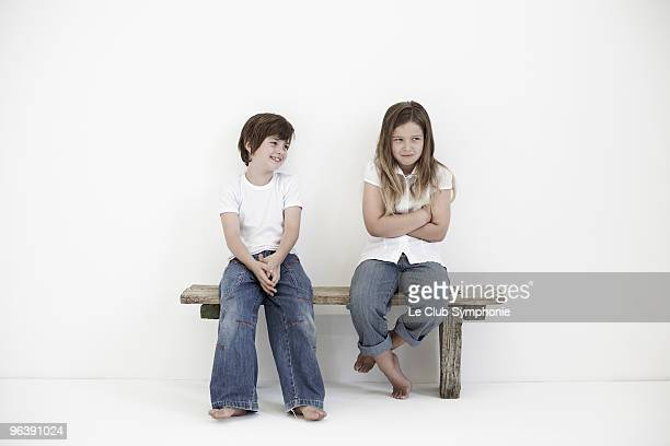 Young boy smiling at shy young girl