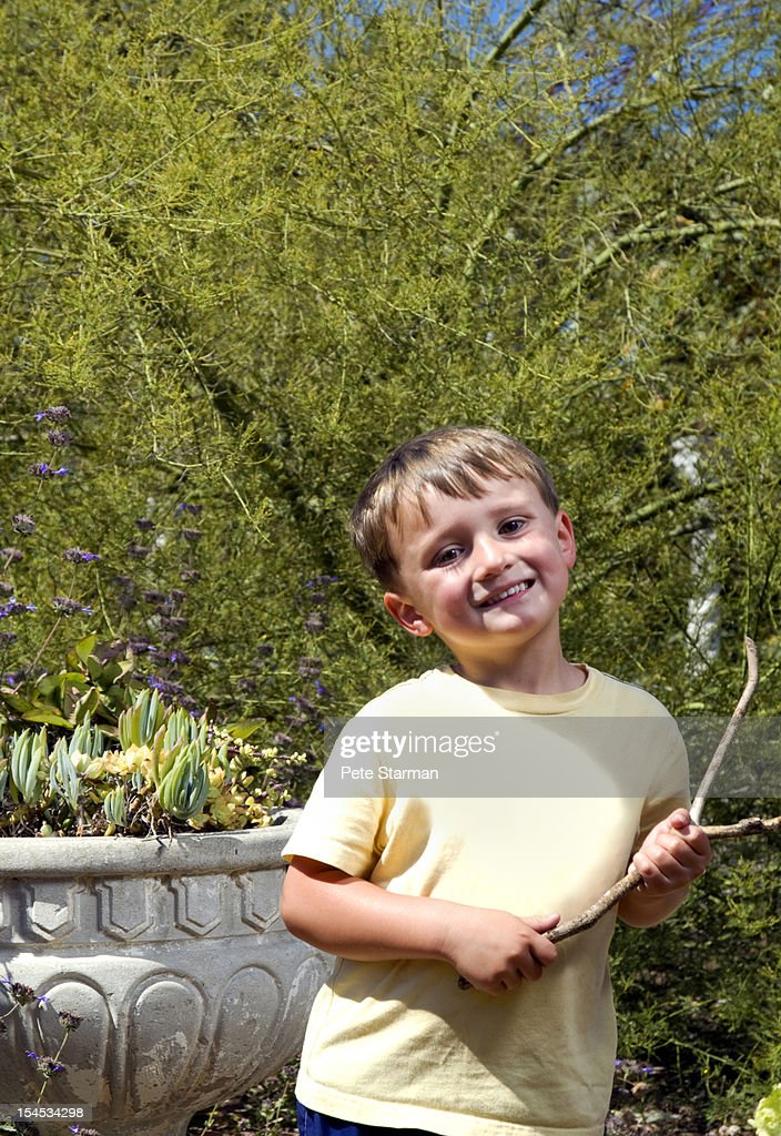 Young boy smiling in a garden holding a stick : Stock Photo