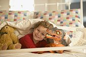 Young boy smiling in bed with toy dinosaur