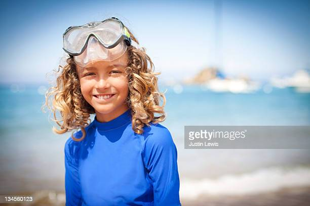 Young boy smiling on the beach with scuba goggles