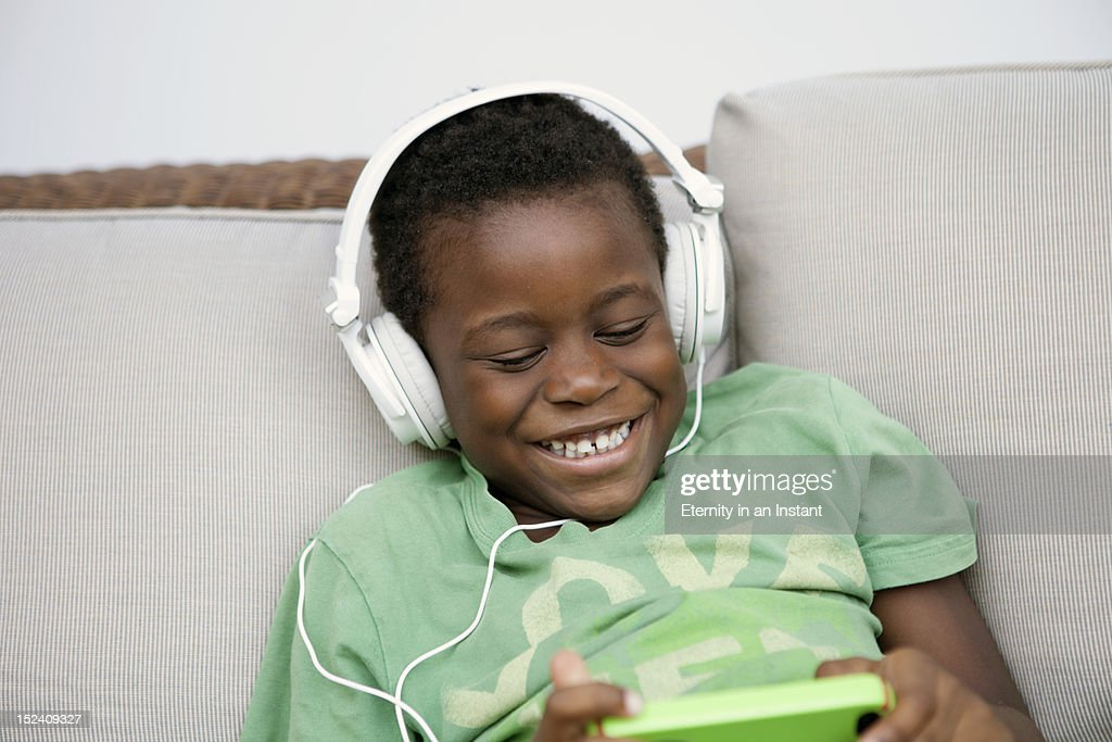 Young boy smiling  playing on smartphone : Stock Photo