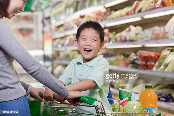 Young boy smiling, sitting in a shopping cart, shopping with mother