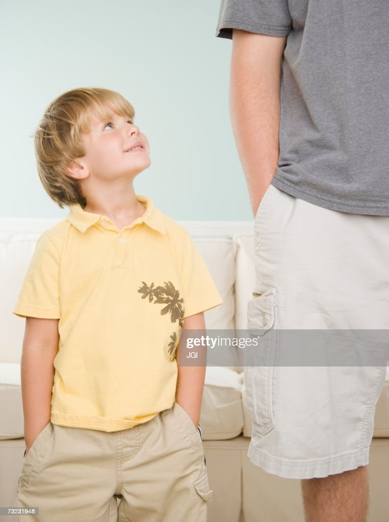 Young boy smiling up at father indoors