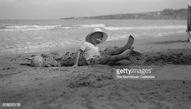 Young boy smiling wearing a straw hat as he falls backwards into a sand dug ditch he has just dug at a sandy beach In the ditch is a toy spade and...