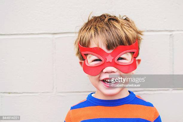 Young boy (2-3) smiling wearing super hero mask