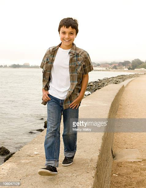 Young boy smiling while walking by the ocean.