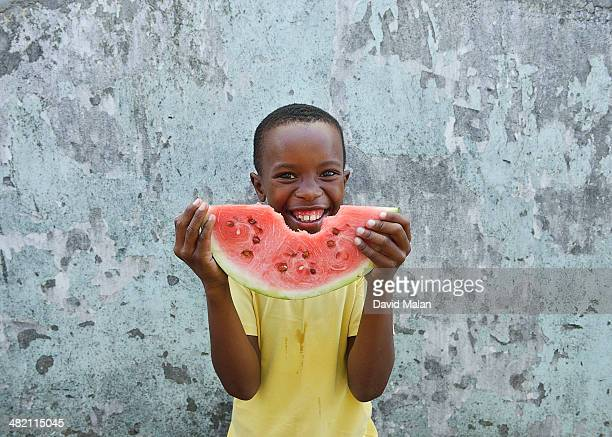 Young boy smiling with a watermelon