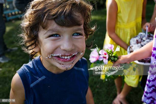 Young boy smiling with birthday cake on his face.