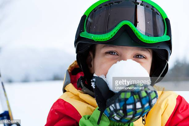 Young boy snowboarder holding snowball
