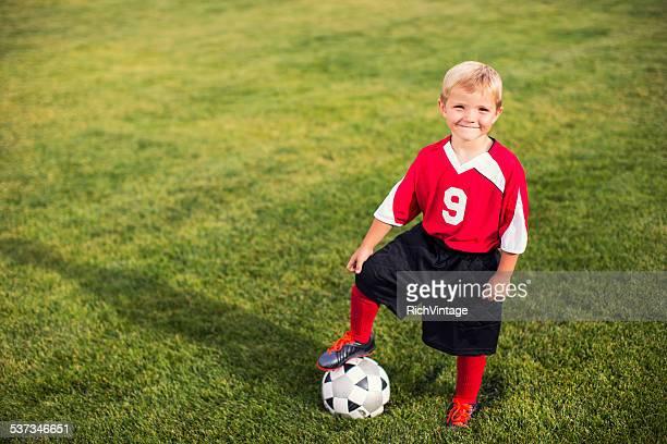 Junge Fußball-Spieler steht auf Gras Feld