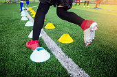 Young boy soccer players Jogging and jump between many marker cones. Soccer player training.