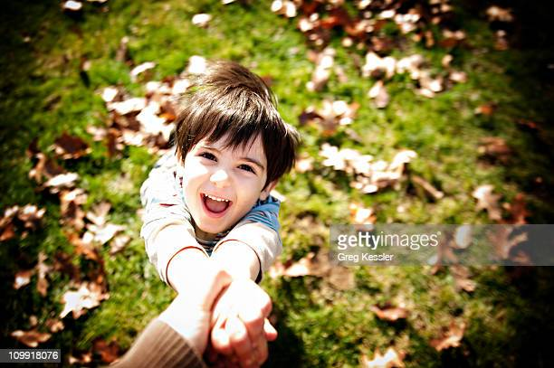 Young boy spinning around in the fall
