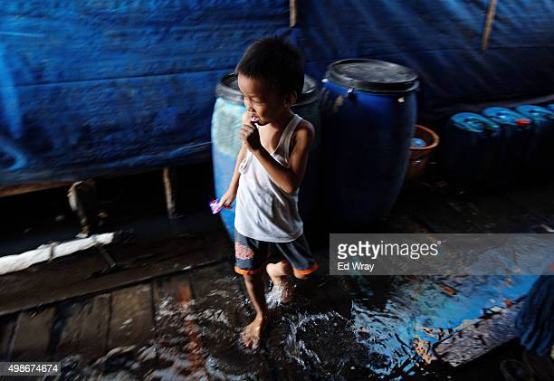 A young boy splashes in water on the floor in his room in a makeshift housing complex which floods every morning with the high tide in the Maura Baru...