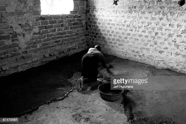 A young boy spreads a new floor at Gulu Crested Crane High School on March 31 2005 in Gulu Northern Uganda Nearly 2 million people have been forced...