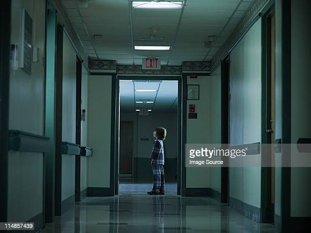 Young boy standing alone in hospital corridor