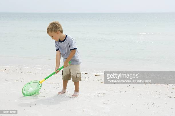 Young boy standing at the beach, picking up ball with net