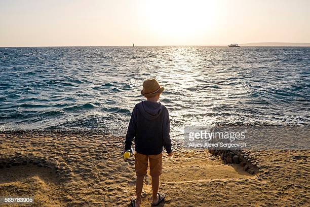 Young boy standing by sea, looking at view, rear view, Hurgada, Red Sea, Egypt