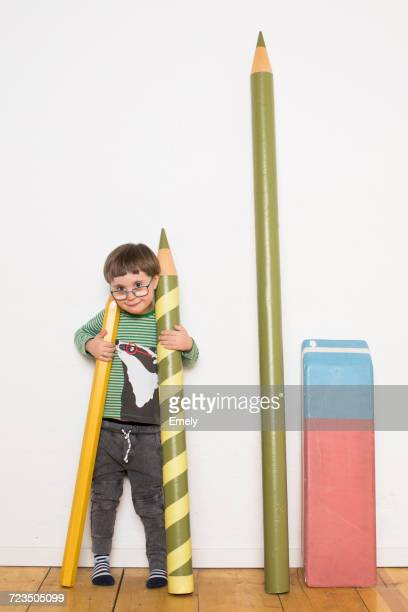 Young boy standing, holding giant size pencils, giant stationery leaning on wall beside him