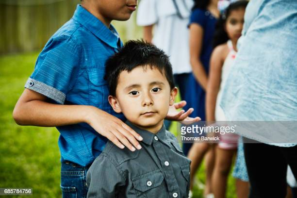 Young boy standing in backyard with brother during family birthday party