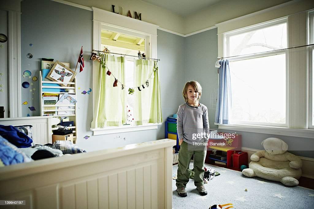Young boy standing in bedroom