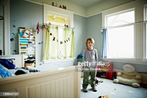 Young boy standing in bedroom