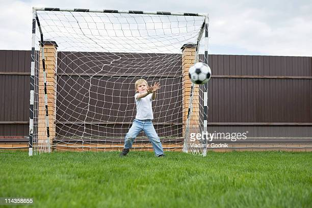 young boy standing in football goal catching ball