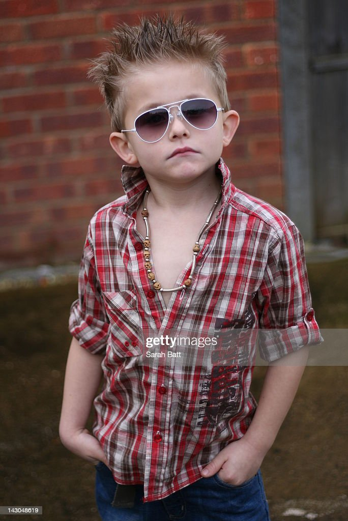 Young boy standing in front of wall : Stock Photo