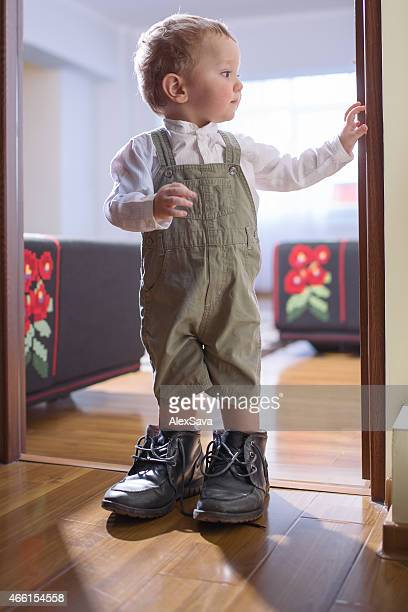 Young boy standing in his father's shoes by the doorway