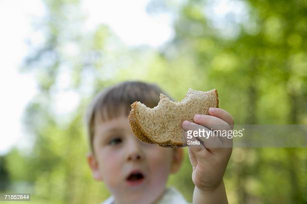 Young boy standing in park and holding slice of bread