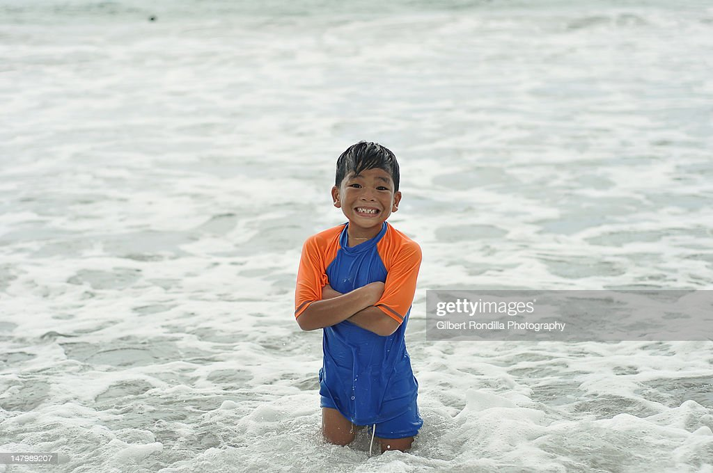 Young boy standing in sea : Stock Photo