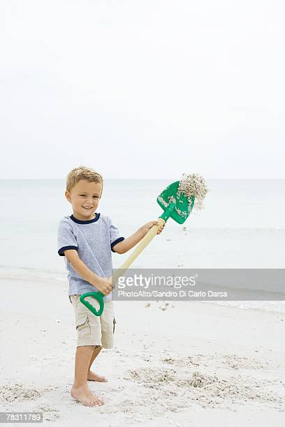 Young boy standing on beach, holding up shovel, throwing sand