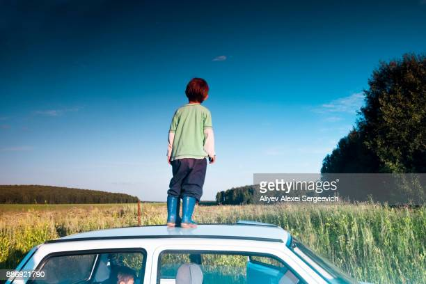 Young boy standing on car, looking at rural view, rear view, Ural, Sverdlovsk, Russia, Europe