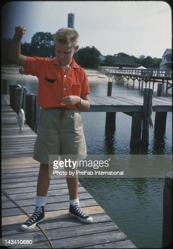 Young boy standing on dock : Stock Photo