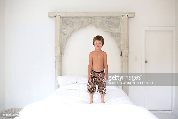 Young boy standing on ornate bed at home