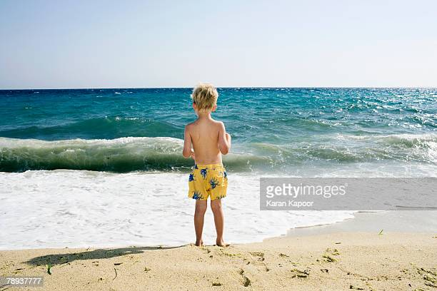 Young boy standing on the beach.