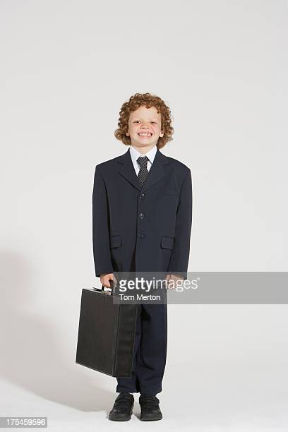 Young boy standing outdoors in business suit