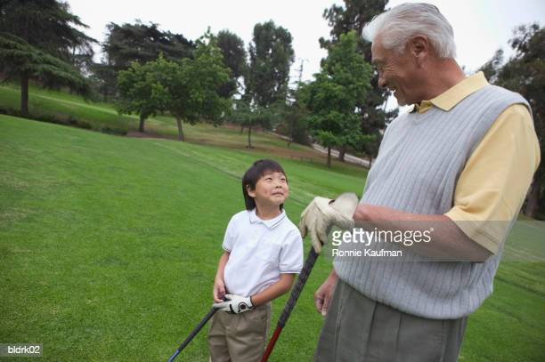 Young boy standing with am senior man at a golf course
