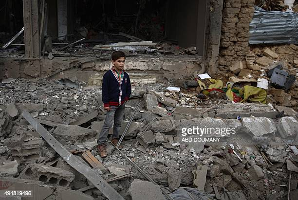 A young boy stands amid debris following a reported air strike by Syrian government forces in the rebelheld town of Douma east of the capital...