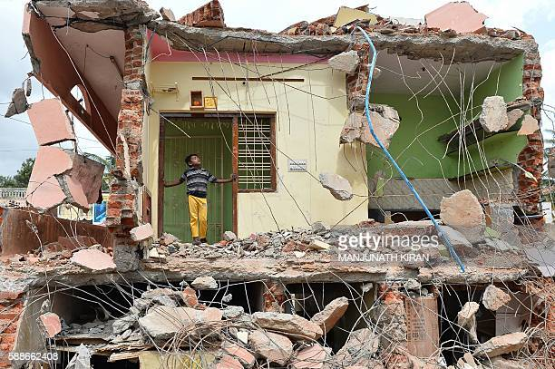 TOPSHOT A young boy stands amidst the debris of demolished houses a day after Bangalore's municipal authority Bruhat Bengaluru Mahanagara Palike...